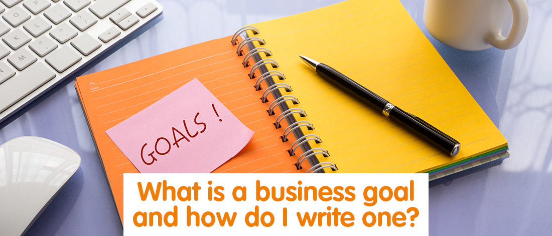 NOtebook with a post it note saying 'Goals'